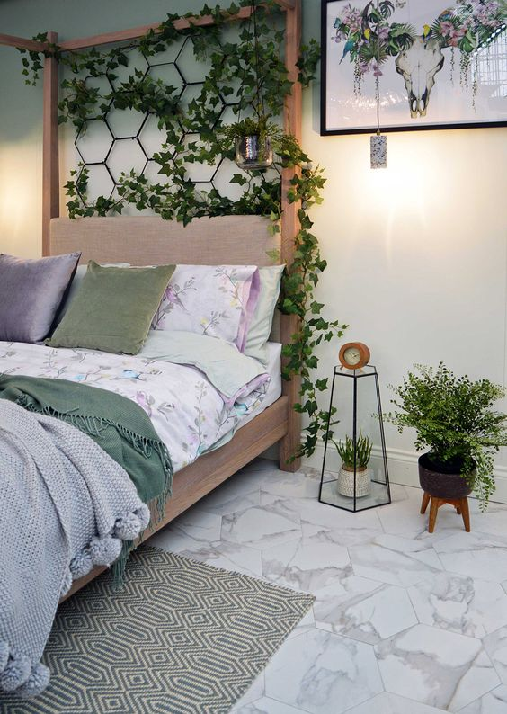 a peaceful bedroom with a wooden bed, a hexagon grid with greenery, floral bedding, potted plants and a pretty artwork