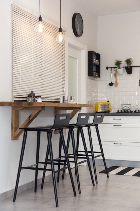 a wooden wall mounted kitchen bar counter with black stools can be used for drinks and meals here