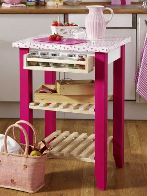 a bold and plyaful IKEA Bekvam cart with hot pink paint, a polka dot countertop, spice racks, wood slab shelves