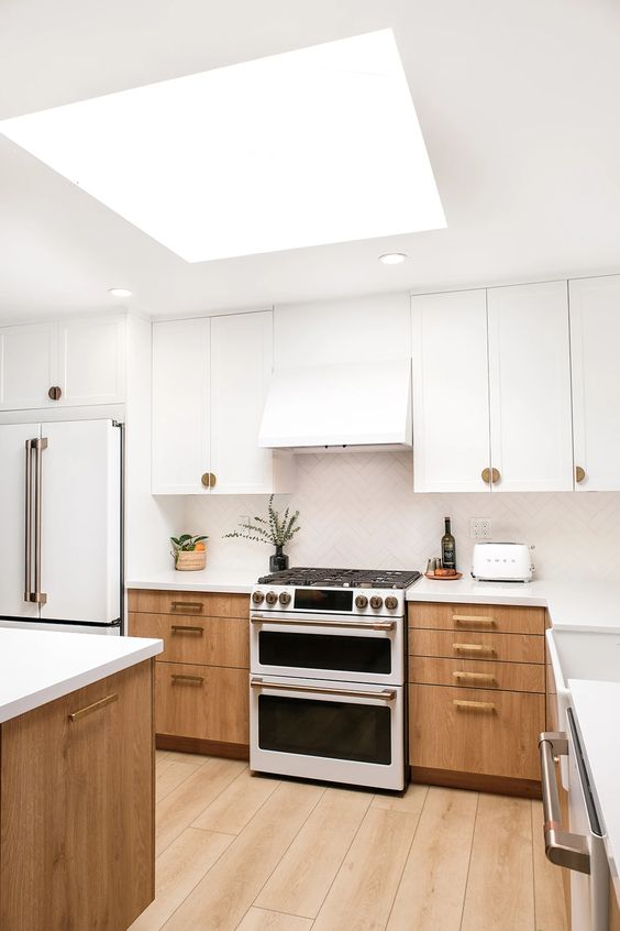 a chic kitchen with white and light stained cabinetry, a white tile backsplash and white stone countertops plus a skylight