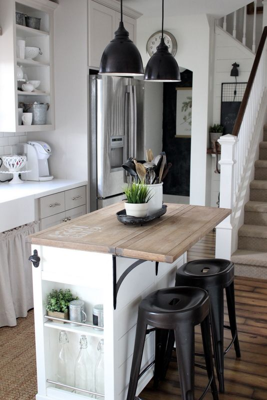 a neutral retro kitchen with white subway tiles, a small kitchen island with storage and a folding countertop plus black pendant lamps