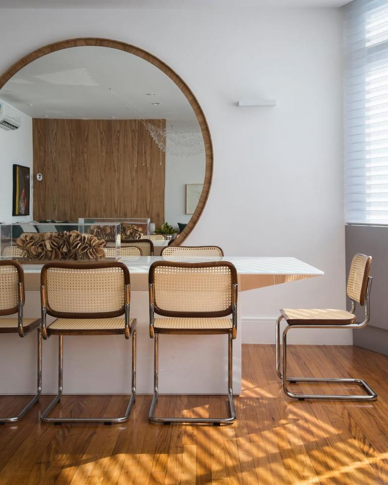 26 a stylish modern dining room with an oversized round mirror in a wooden frame, a statement table and rattan chairs