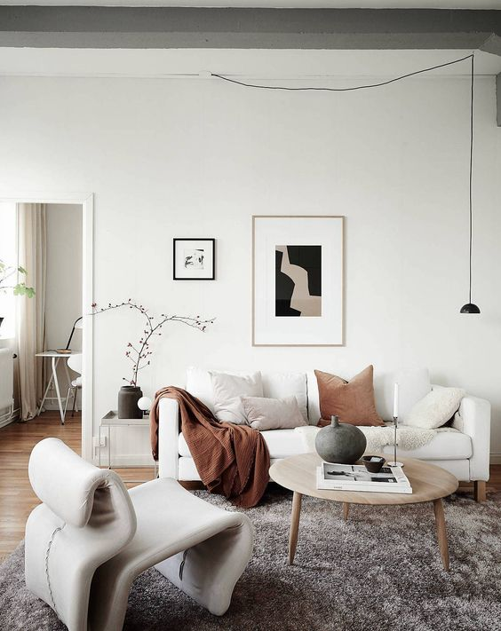 26 a stylish neutral living room with a white Stockholm sofa, a neutral chair, a round wooden table and a pendant lamp