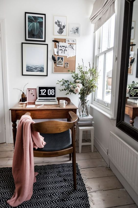 a stylish retro workspace by the window, with a stained desk and a black leather chair, a lovely gallery wall that creates a mood