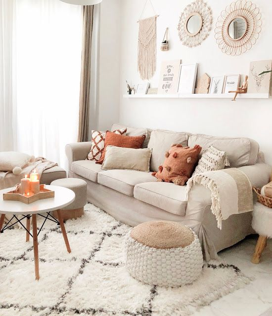 a neutral boho living room with a grey Ektorp sofa, stools and ottomans, a ledge with artworks and mirrors and a round table