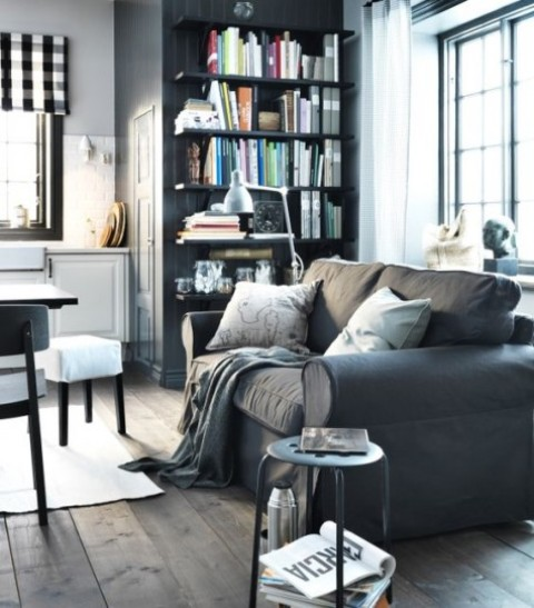 a modern farmhouse space with a grey bookcase, white cabinets, a dark table and white chairs and a grey Ektorp sofa