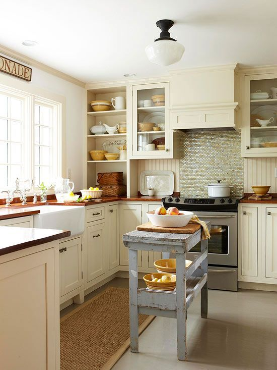 a neutral warm-colored kitchen with green tiles, butcherblock coutnertops and a blue shabby chic kitchen island