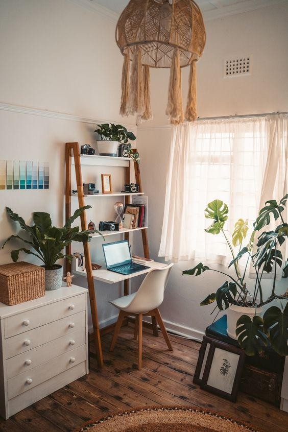 a lovely boho working space with a ladder like desk with shelves, a white chair, lots of potted plants and a macrame lampshade