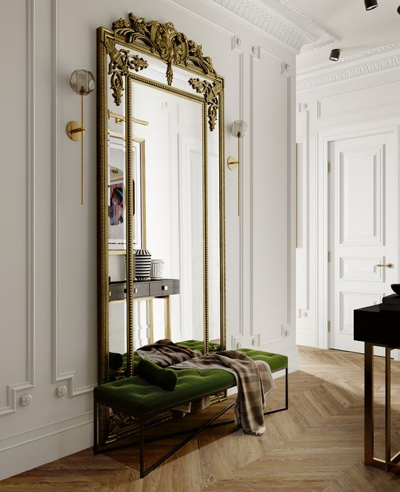 29 a luxurious entryway with a green velvet bench, an oversized mirror in a refined gilded frame and a dark console table