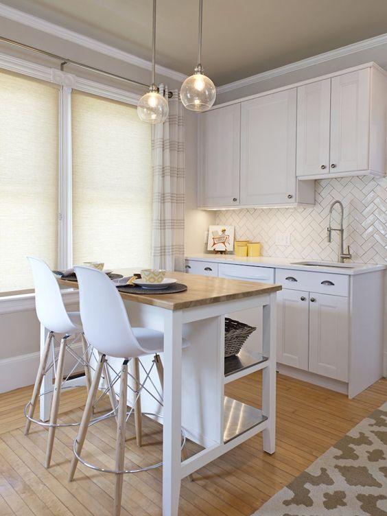 a small white kitchen with a herringbone backsplash, a small white kitchen island with a butcherblock countertop and pendant lamps
