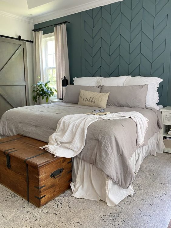 30 a catchy bedroom with a slate blue accent wall, neutral furniture, a wooden chest for storage and neutral textiles