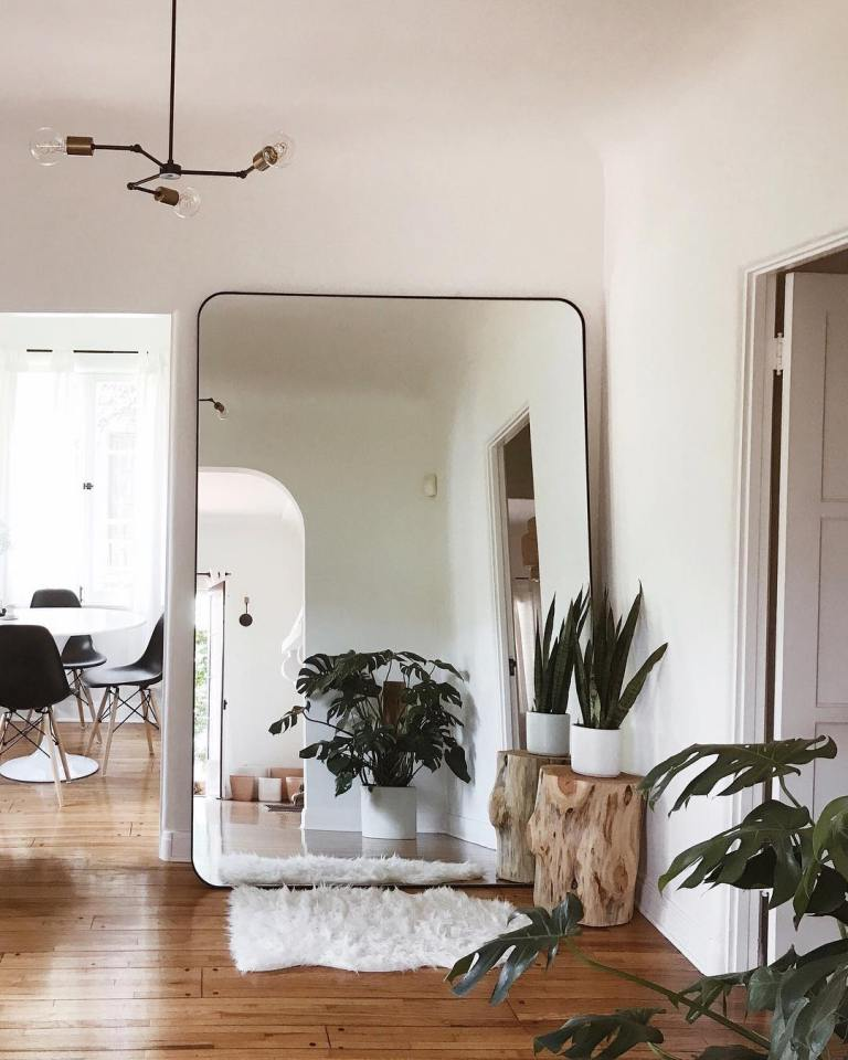 a modern boho nook with an oversized mirror in a sleek black frame, potted plants and a faux fur rug is chic and cozy