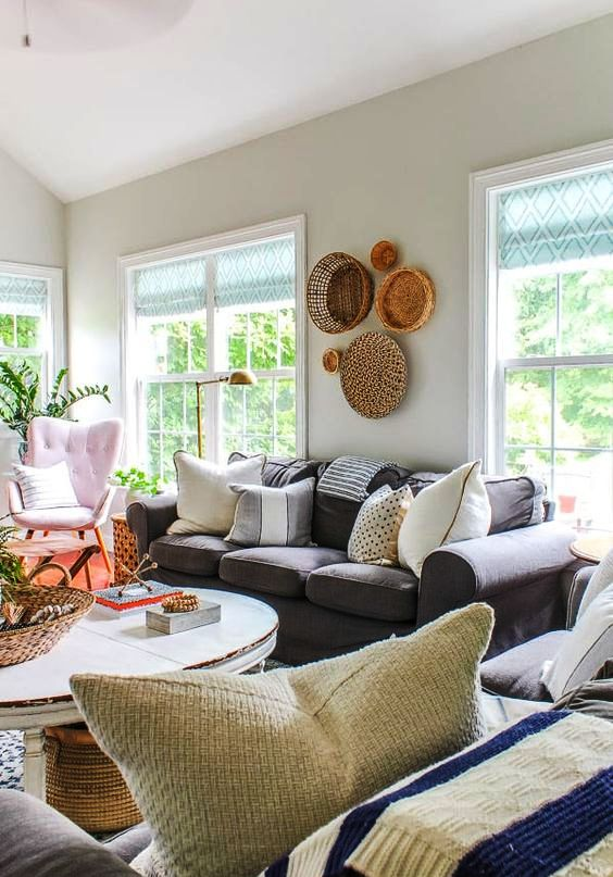 a pretty and vivacious farmhouse living room with a grey Ektorp, a lilac chair and ottomans, a round table and decorative baskets
