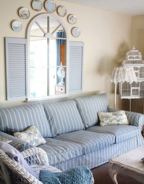 a striped blue and white Ektorp sofa cover, shutters, decorative plates and white rattan furniture for a seaside interior