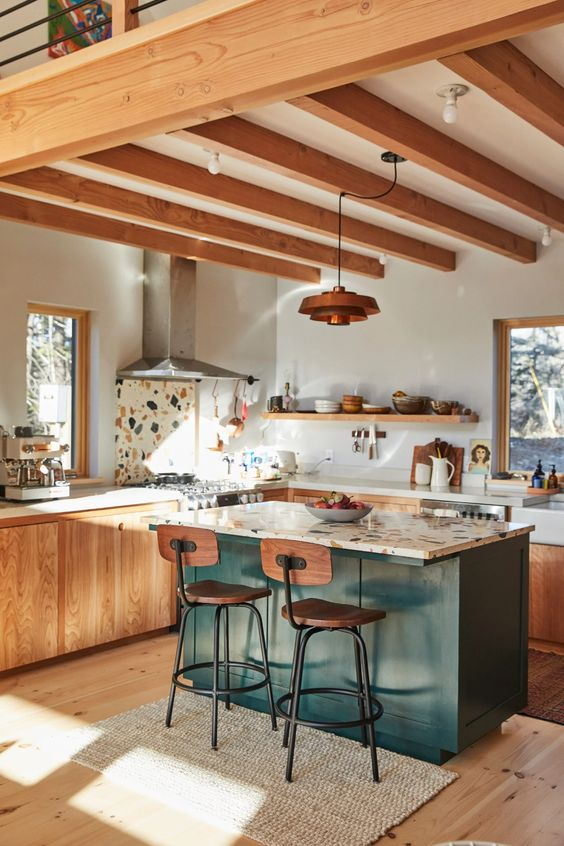 a stylish light stained modern kitchen with matching wooden beams and a green kitchen island with a terrazzo countertop that makes an accent