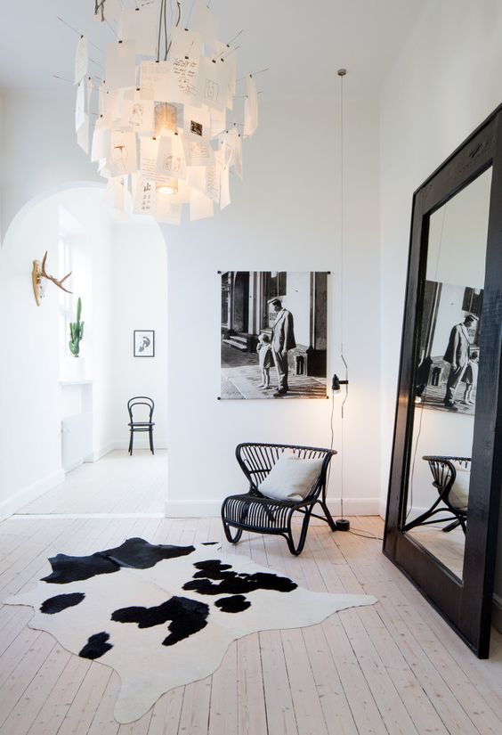 a bold black and white Nordic space with a black rattan chair, an oversized mirror in a black frame, a catchy note chandelier