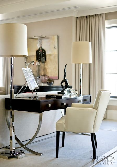 a refined living room in neutrals, with dark furniture for a contrast, a dark desk and a creamy chair, floor lamps is very chic