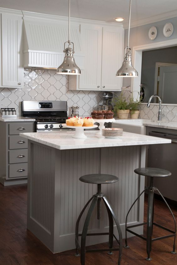 The original wrap-around countertop was replaced with a space-saving kitchen island and breakfast bar with modern barstools.  All new appliances, an attractive vent hood, marble countertops and pendant lights were installed, and the tile backsplash adds an unique flair, as seen on HGTV's Fixer Upper.  (detail)