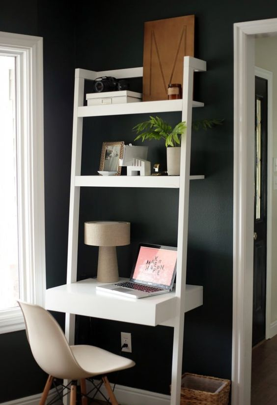 a tiny working nook with a white unit with shelves, a desk with drawers, potted plants and photos in frames is cool