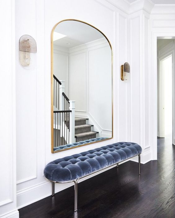 33 a refined minimalist entryway with a pretty arched mirror in a gilded frame, a blue uphalstered bench and sconces