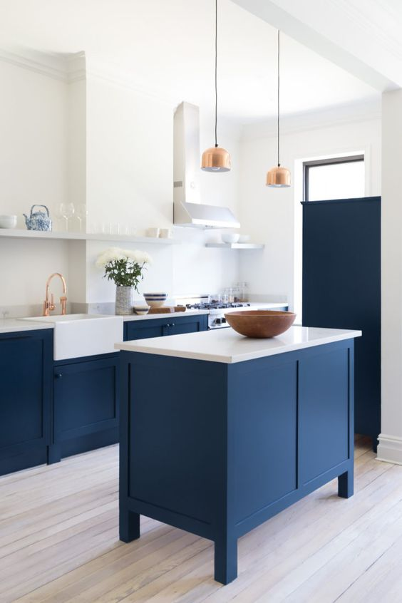 a super stylish navy and white modern kitchen with copper touches and a small kitchen island that matches the cabinetry