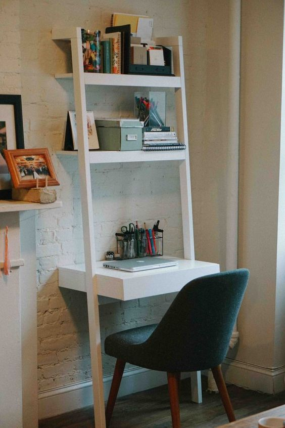33 a white ladder-style storage unit with shelves and a desk space, with boxes, books and other stuff and a black chair