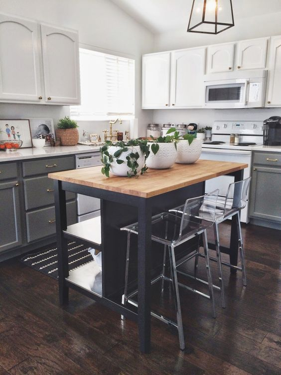 a two-tone kitchen in white and grey, with white countertops, a small black kitchen island with storage and eating for a contrast