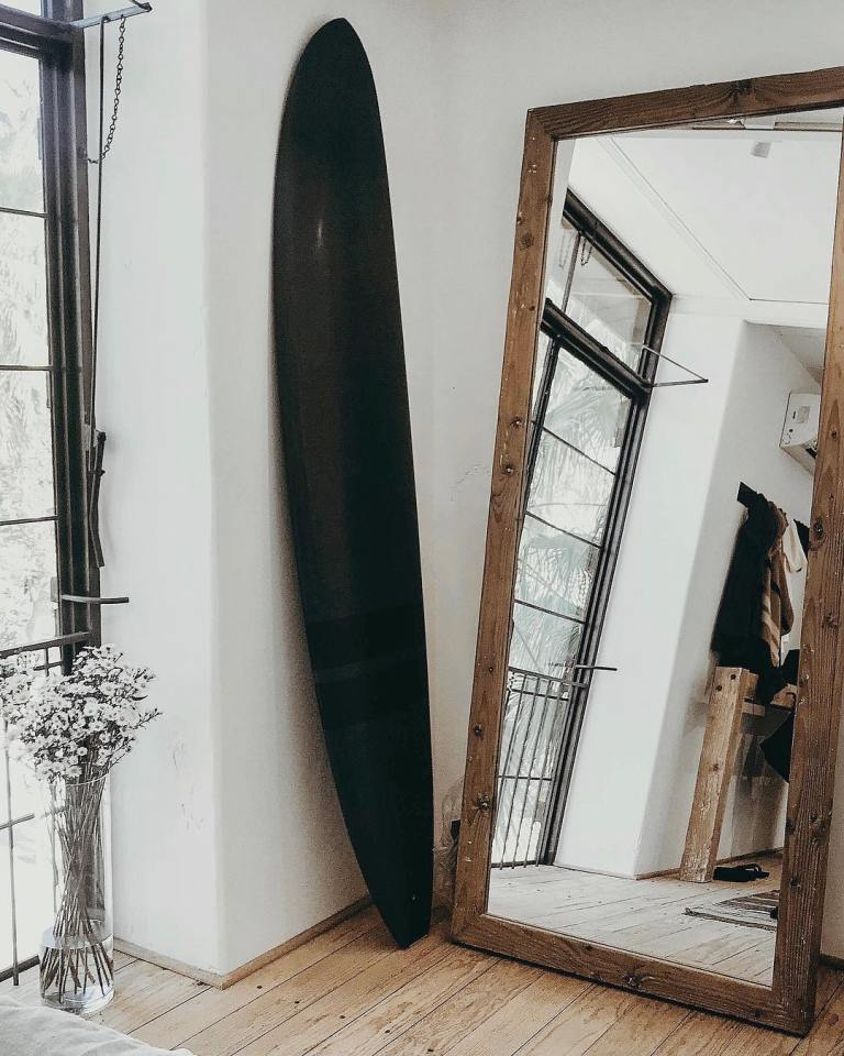 34 an entryway with an oversized mirror in a rough wooden frame, a surf for a relaxed touch and racks