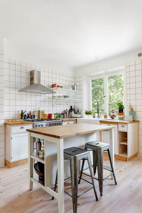 a welcoming white modern kitchen with square tiles, butcherblock countertops, a small kitchen island with storage and an eatign surface