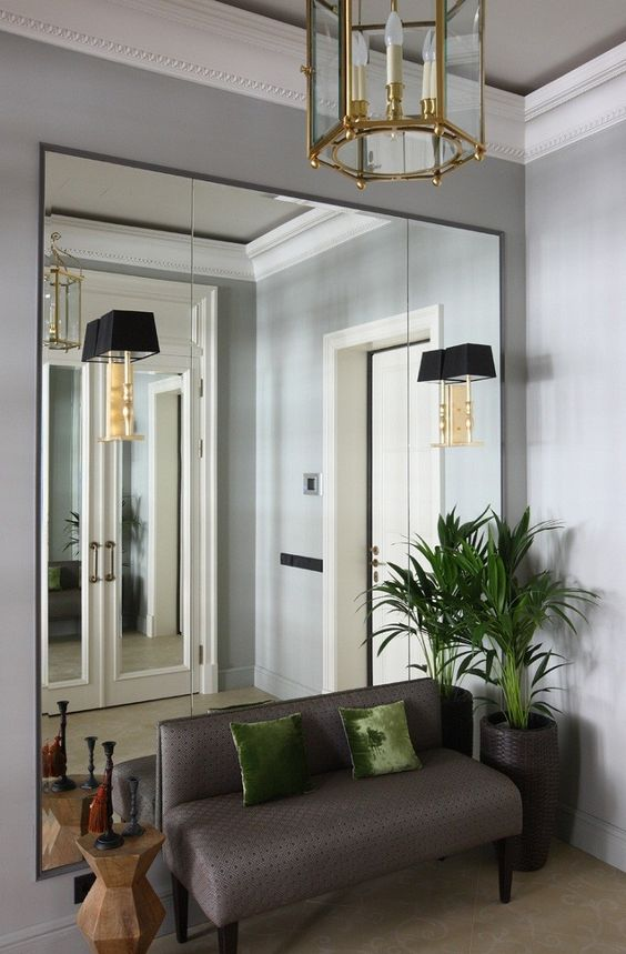an exquisite entryway with an oversized mirror, a taupe bench, potted plants, a geometric table and a glass chandelier