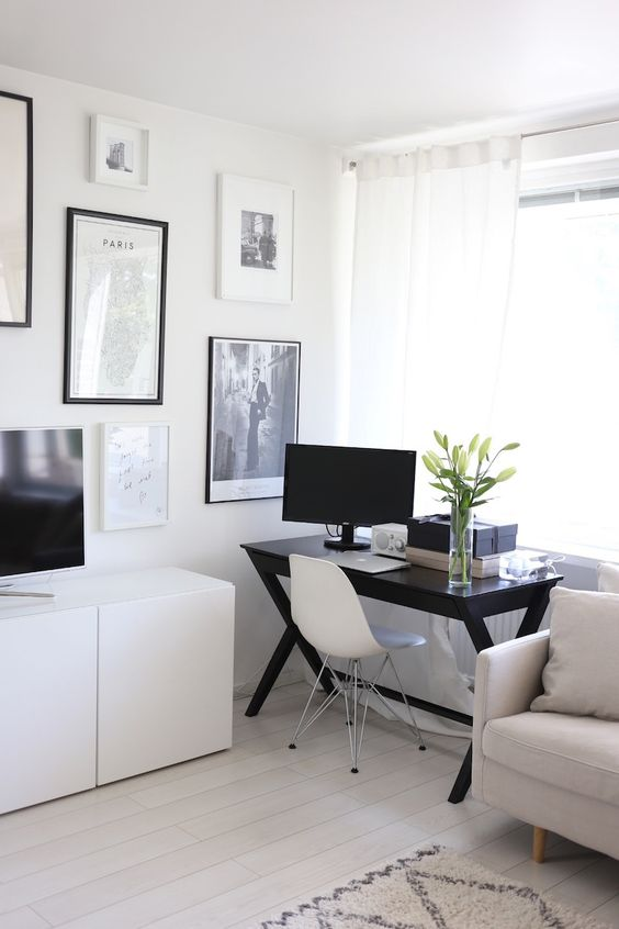 a Scandinavian living room with neutral furniture, a black desk by the window, a monochromatic gallery wall and a TV