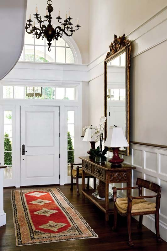 36 an exquisite entryway with heavy vintage furniture, a large mirror in a gilded vintage frame, a vintage chandelier and a bold rug