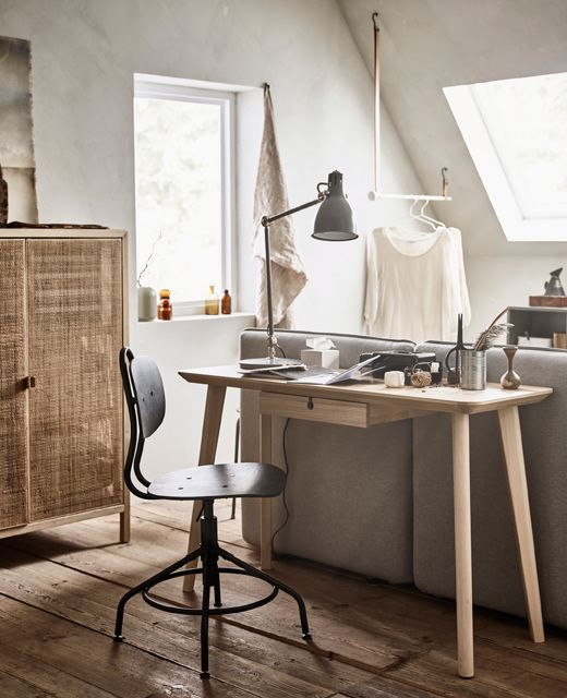 a Scandinavian space with IKEA furniture, a sleek and small desk behind the sofa and a vintage metal chair and a lamp