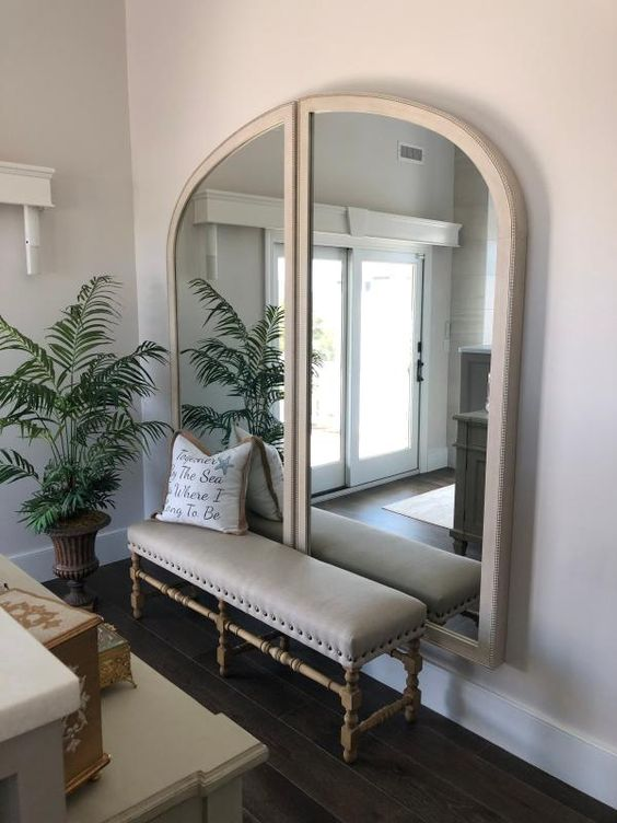 38 a cozy and chic entryway with a lovely upholstered bench, an arched mirror of two halves, a white sideboard
