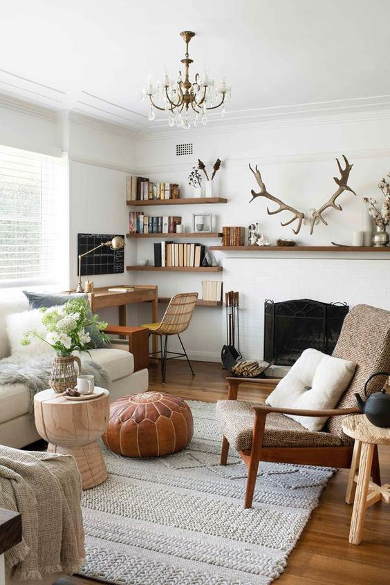 a stylish modern living room done in neutrals, with a vintage fireplace, chic and comfy furniture, a small workspace in the corner, floating shelves and antlers