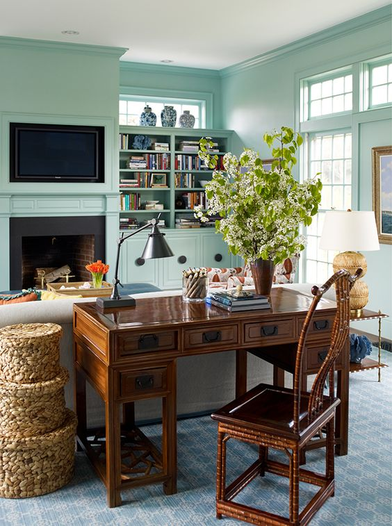 41 a vintage living room with mint blue walls, a built-in fireplace, a vintage heavy desk and a chair, a stack of baskets for storage