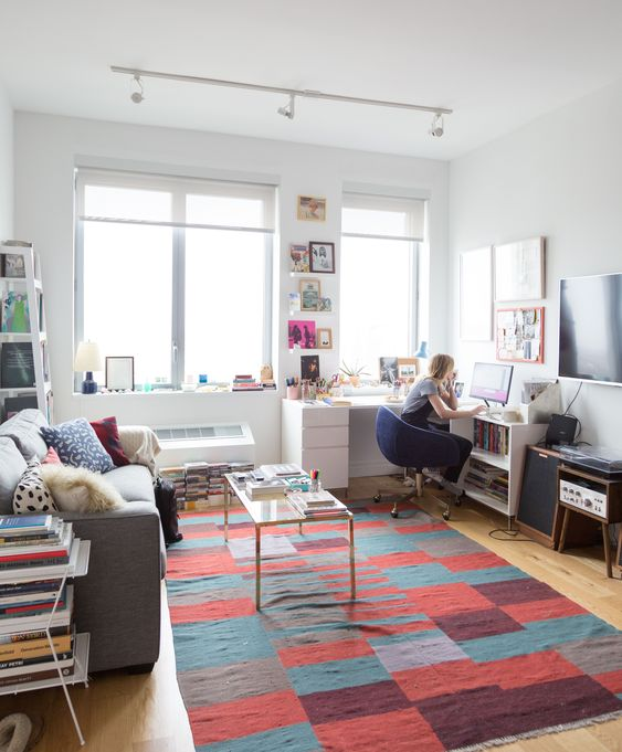 a vivacious living room with modern furniture, colorful art, books and a rug plus a corner desk for working there