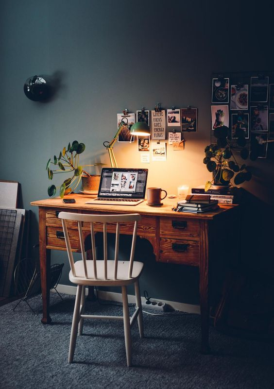 a Nordic home office with a vintage stained desk, a white chair, potted plants and a simple gallery wall with photos