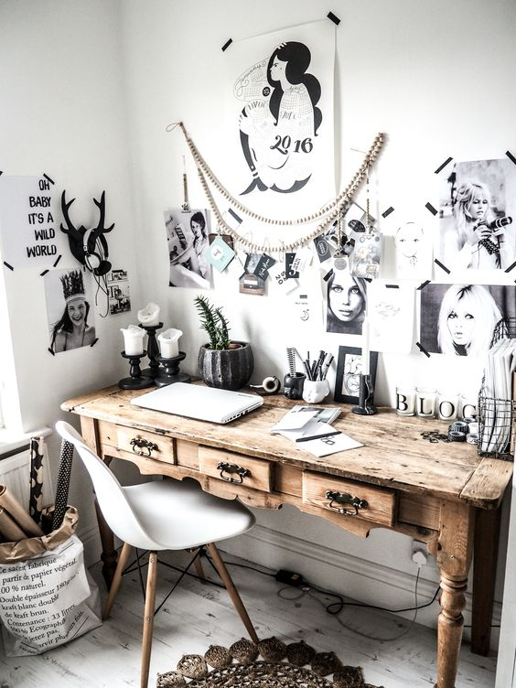 a Nordic home office with a wooden vintage desk, a white chair and a black and white gallery wall with no frames