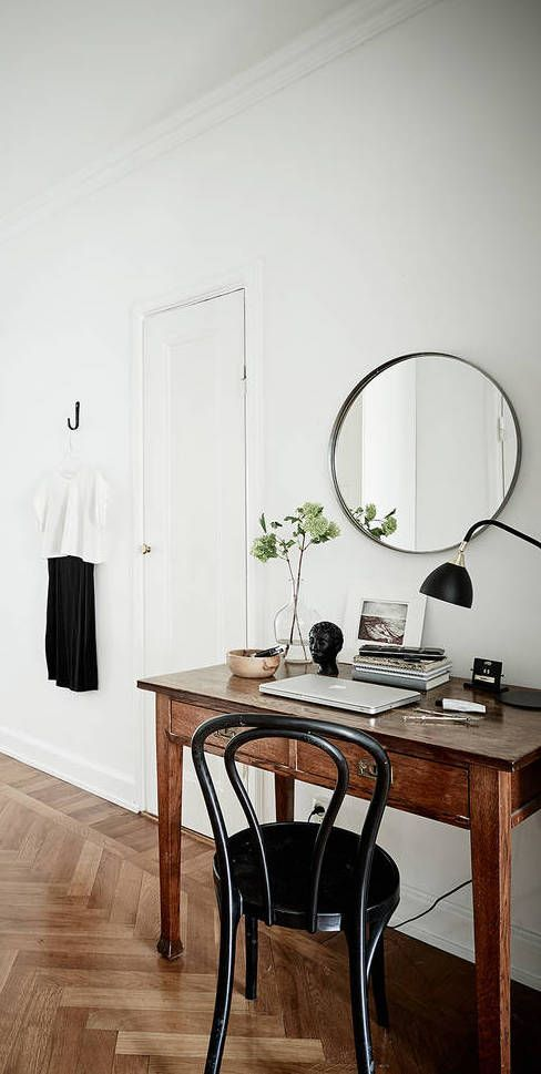 a Nordic space with a dark stained wooden desk, a black chair, a round mirror, a table lamp and some greenery in a vase