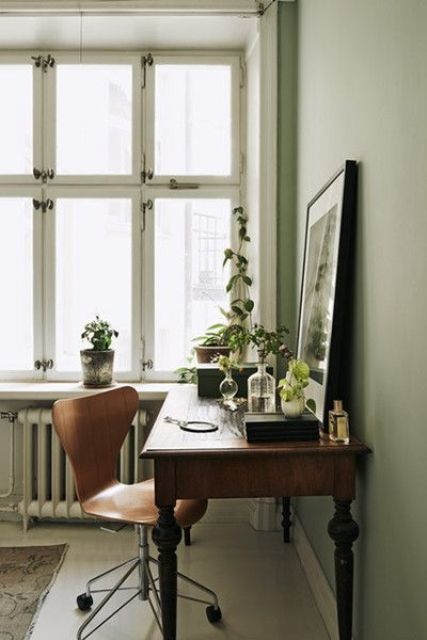 a Nordic working space with a vintage stained desk, a plywood chair, lots of plants and a statement artwork right on the desk