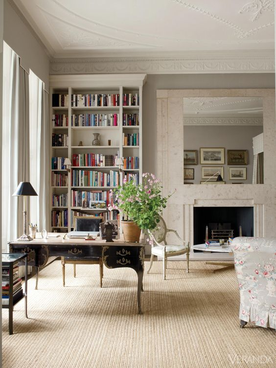 a Parisian home office with a built-in bookcase, a black and gold vintage desk, floral furniture, a fireplace and a statement mirror over it