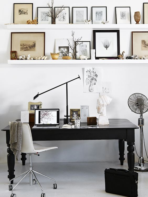 a Scandinavian home office with floating shelves, a black vintage desk, a white chair, a beautiful gallery wall and a fan