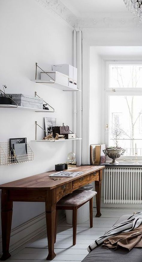 a Scandinavian home office with wall-mounted shelves, a vintage stained wooden desk, a matching stool and a vintage bowl with plants