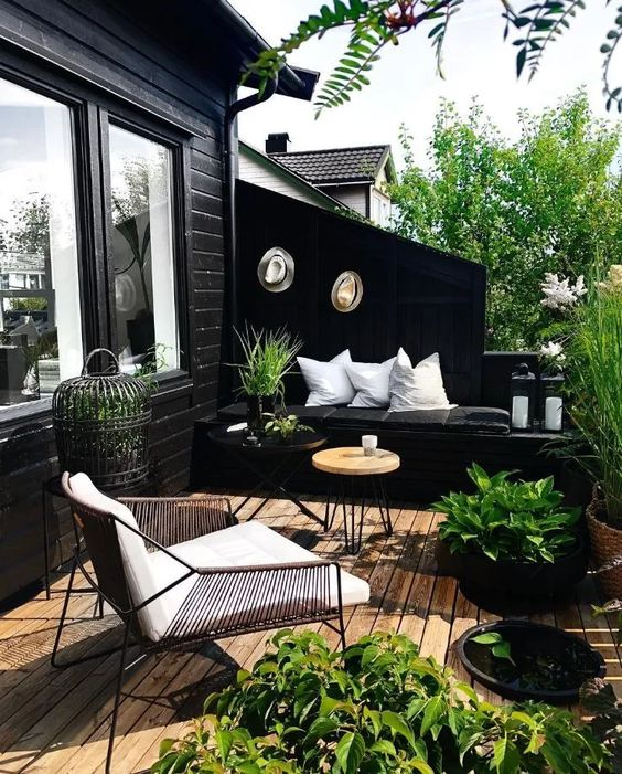a Scandinavian summer balcony with black and white furniture and pillows, a candle lantern and some potted greenery and blooms