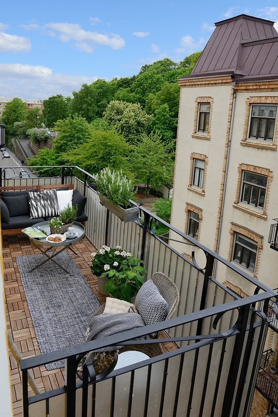 a Scandinavian summer balcony with rattan chairs, a sofa with pillows, potted blooms, a rug and a small table
