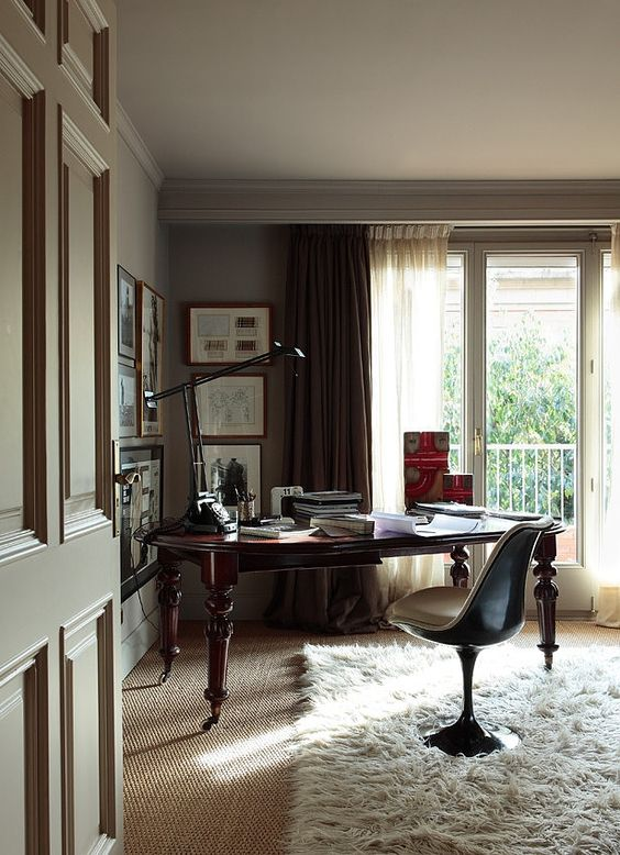 a beautiful dove grey home office with a monchromatic gallery wall, a dark stained desk and a pretty chair plus a table lamp