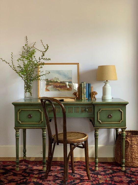 a beautiful green vintage desk with gold touches, a vintage chair, a basket and a boho rug create a chic and elegant space