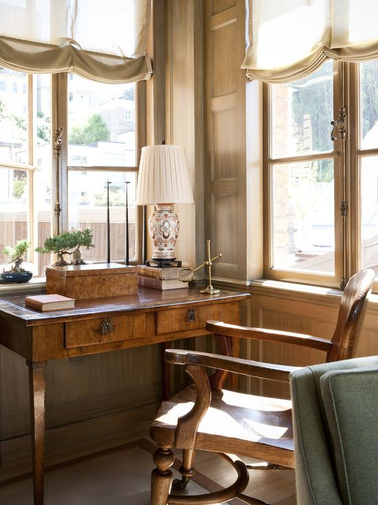 a beautiful home office with a stained wooden desk, a wooden chair, a table lamp and some neutral curtains