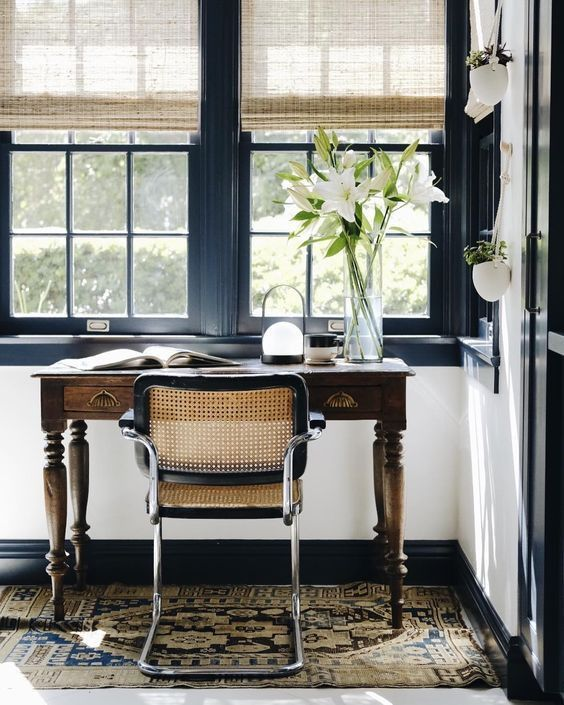 a beautiful home office with navy framed windows, a vintage stained desk, a rattan chair and shades plus a boho rug